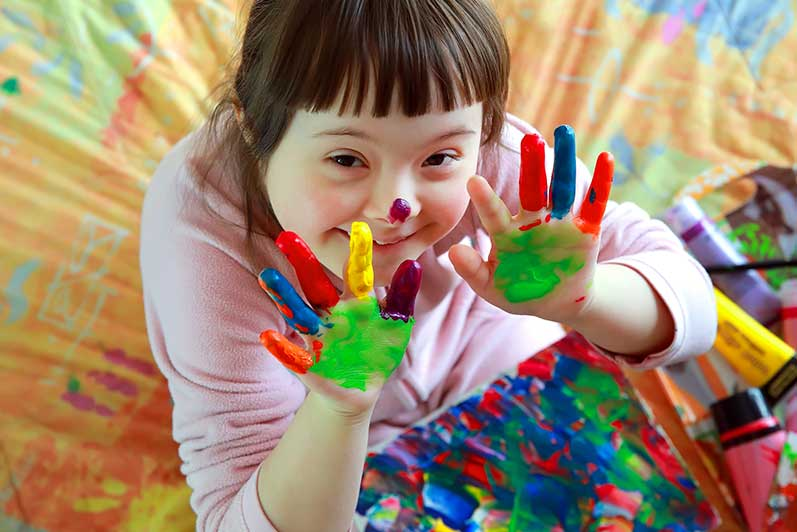 Photo of girl with down syndrome smiling while showing her hands covered in colorful paint